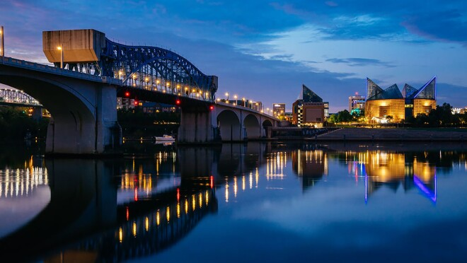 The Tennessee river at night, with a bridge stretching along it's width. In the foreground, Chattanooga buildings are lit up.
