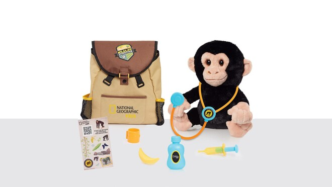 An image of a brown backpack with a stuffed monkey toy next to it. The monkey toy has a stethoscope on its ears. There are other accessories like a bottle and a banana in front of the monkey and the backpack.