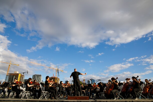 In front of a clear, blue sky, with a few buildings and cranes visible, the Amazon Symphony Orchestra performs at the closing ceremony. In this image, a conductor is seen on a platform, surrounded by orchestra members with string-based instruments.
