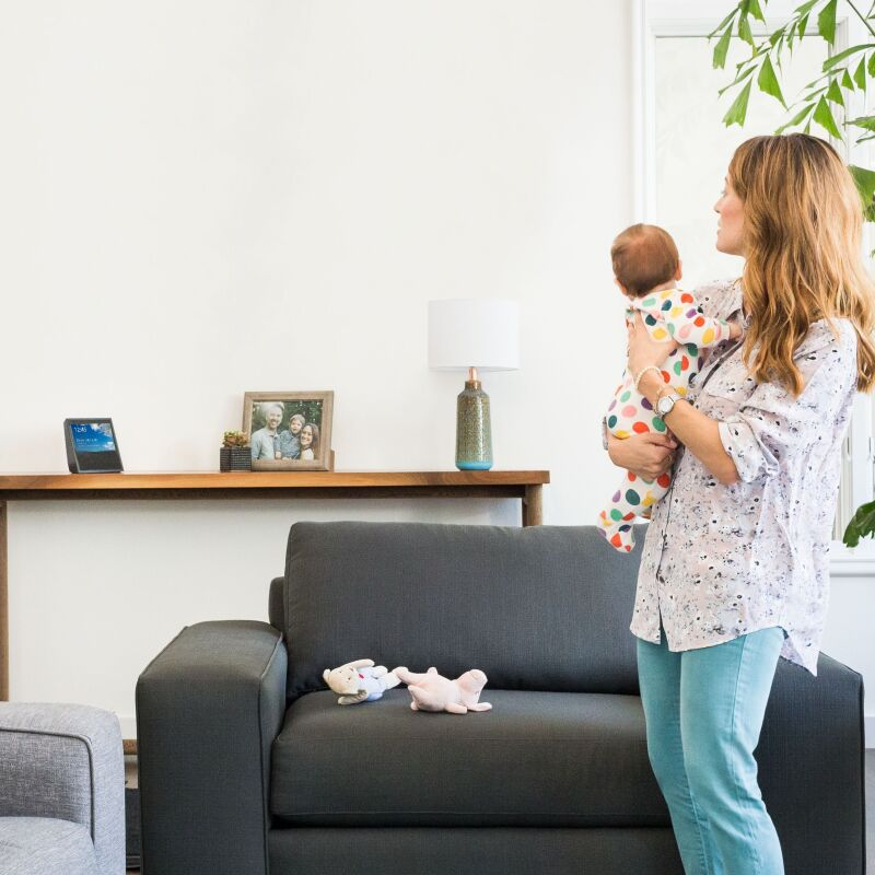 An Amazon Echo Show on a console table in a home with a mom and baby.