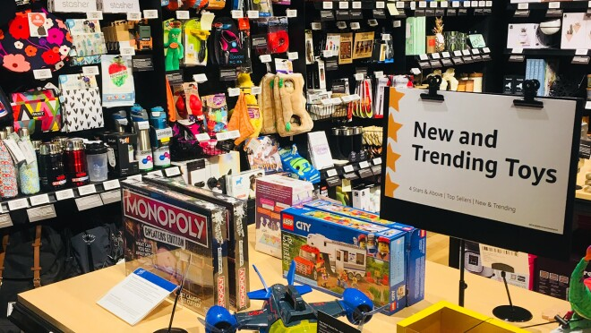 """A table of """"New and Trending Toys"""" at the Amazon 4-star store. On the table are a Monopoly board game, LEGO City set, and COZMO robotic toy. Each product has a digital price tag and a customer review displayed alongside the item. Behind the table are Gifts for Pets, Gifts for Grown-Ups, and Candles & Home Decor."""