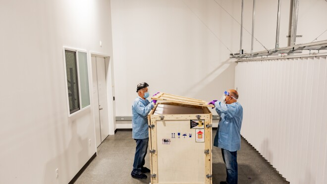 Two men wearing protective clothing, face shield, face mask, and gloves open a large wooden crate.