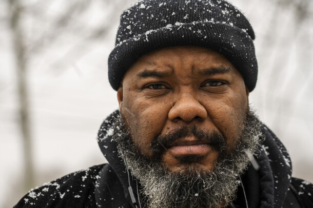 A bearded man in a winter hat stands outside in the snow.
