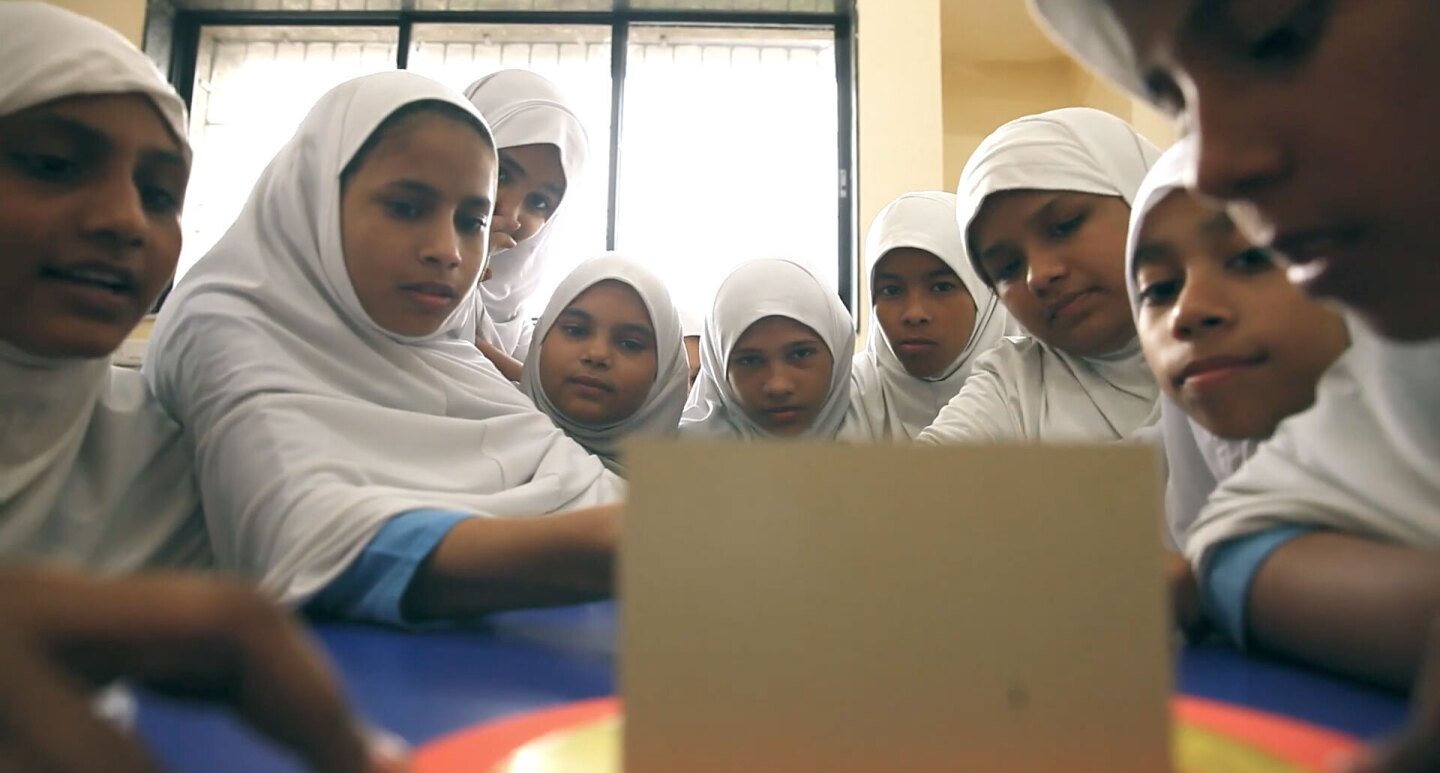 female schoolchildren sit gathered around and facing a small computer screen.