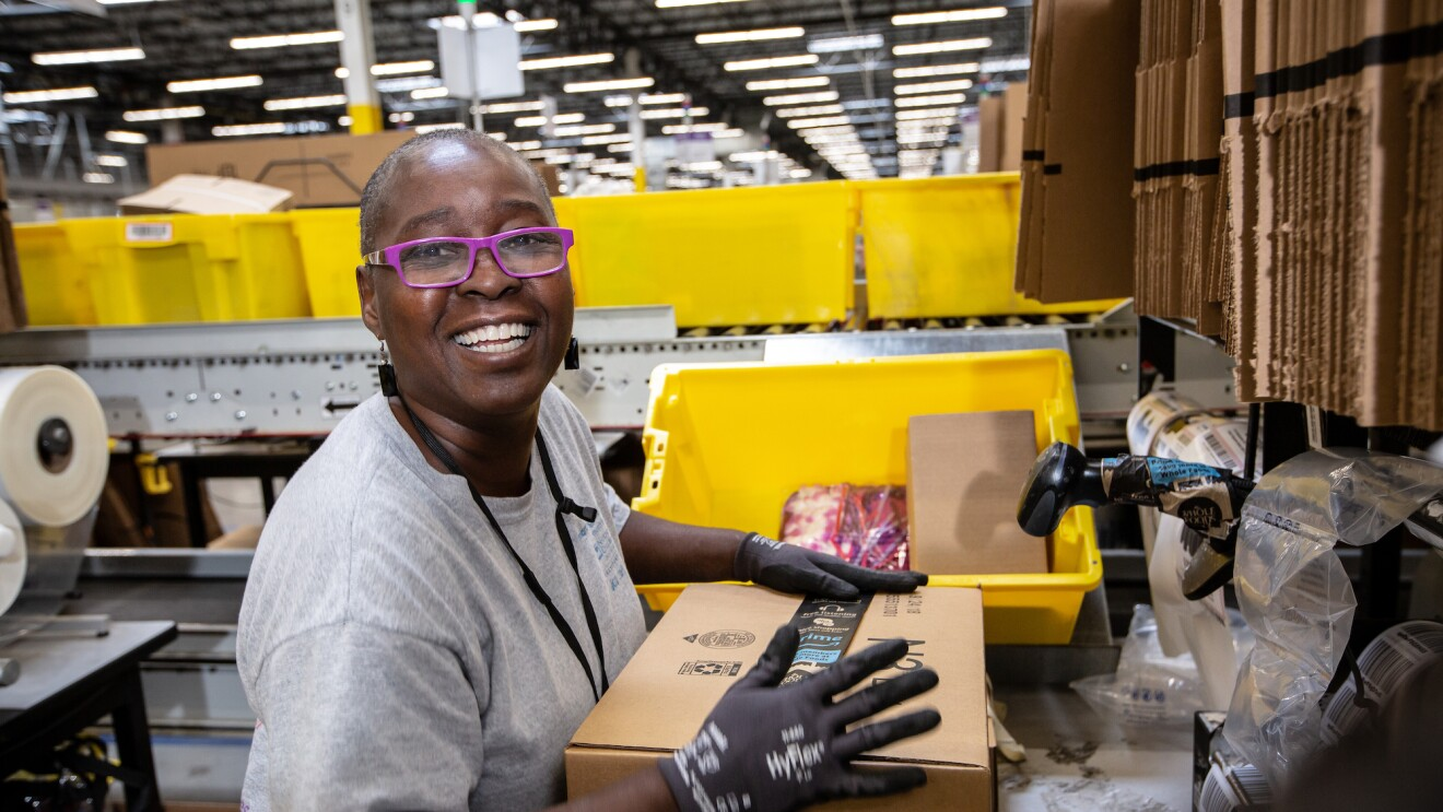 An Amazon Fulfillment Center employee smiles at the camera as she prepares a package for shipment.