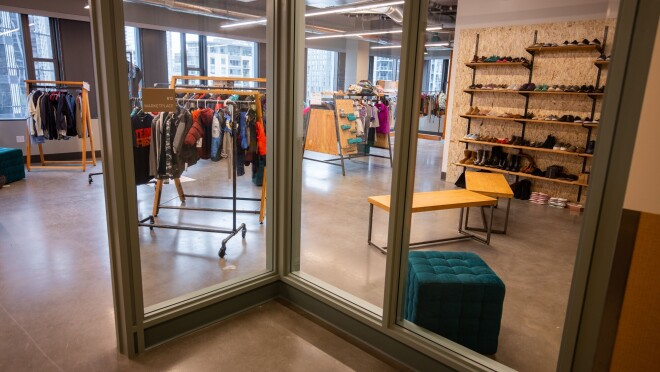 An image looking through a glass wall into a room with clothing on racks and shoes on shelves in a retail store-like setting.