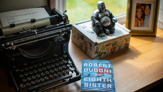 """Author Robert Dugoni's workspace within his home office, a refurbished typerwriter sits near a window. To it's left, a small box topped with a Buddha figurine, a copy of his book """"The Eighth Sister"""" and a framed photograph."""