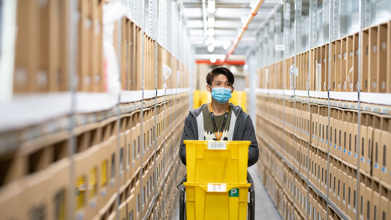 An Amazon employee wearing a face mask pushes a cart with yellow boxes through a fulfilment centre aisle.