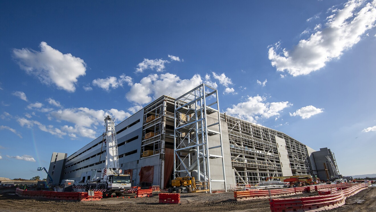 An image of a partially built Amazon fulfillment center with construction barriers and equipment around it. There is a blue sky overhead.