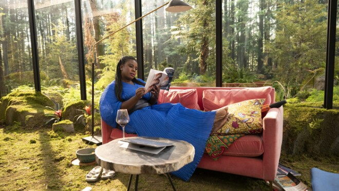 An image of Uzo Aduba sitting on a coach in a home that has large windows showing a green landscape outside and green grass coming through the home as carpet. She is wearing a bright blue dress that contrasts with the green.