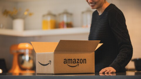 An Amazon box sits on a counter. Behind the box, a person stands, resting their hand on the counter.