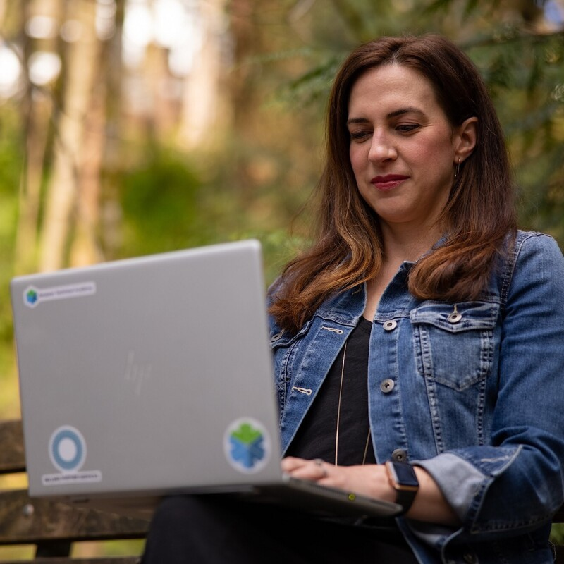 Ashely Rajagopal sits on a bench outside with vibrant greenery behind her. She is focused while she works on her laptop.