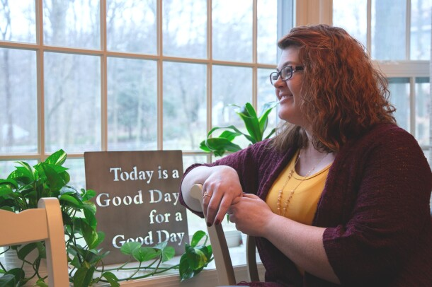 """A woman is photographed in profile standing next to a window. Near her is a sign that says """"Today is a Good Day for a Good Day."""""""