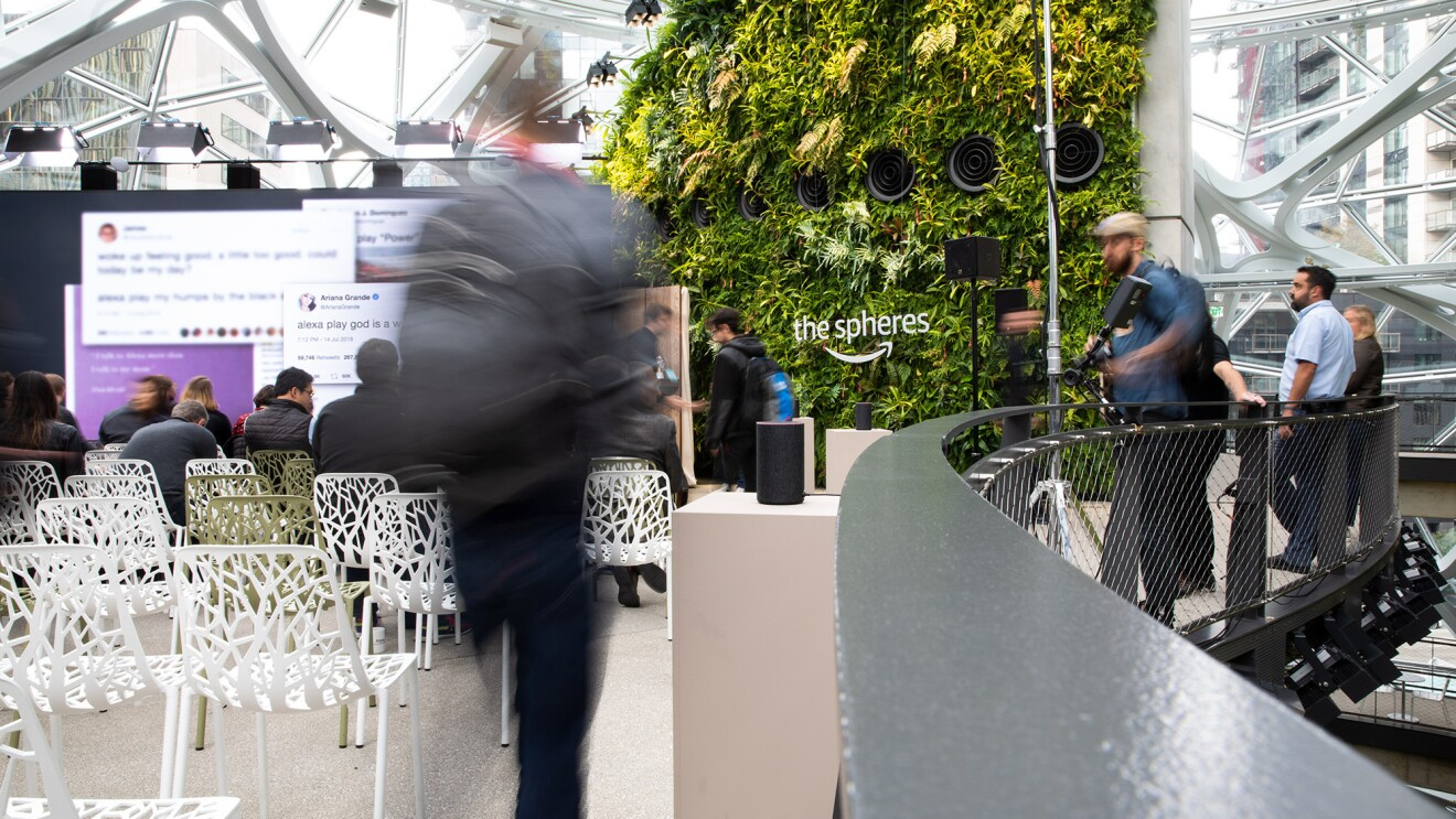 A man walking into the September 2018 Devices announcement event. To the left are chairs in front of a large screen. To the right others stand against a railing. Behind the scene is a living wall in The Spheres.
