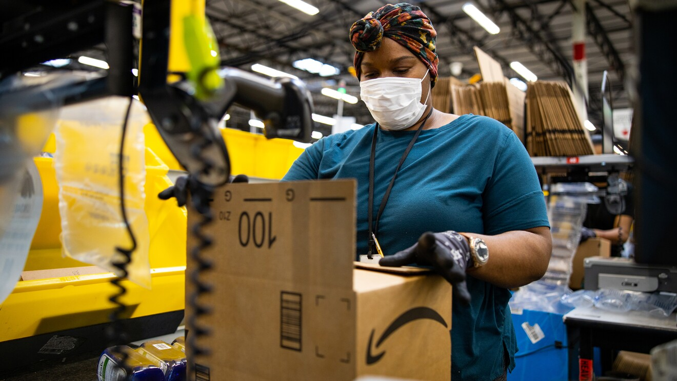 A woman working at an Amazon Fulfillment center wears a headwrap, a face mask, and gloves as she prepares a customer order.