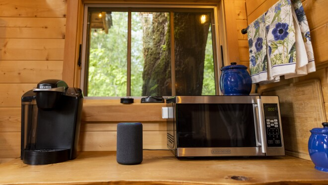 An Amazon Echo on a counter with a microwave and coffeemaker.