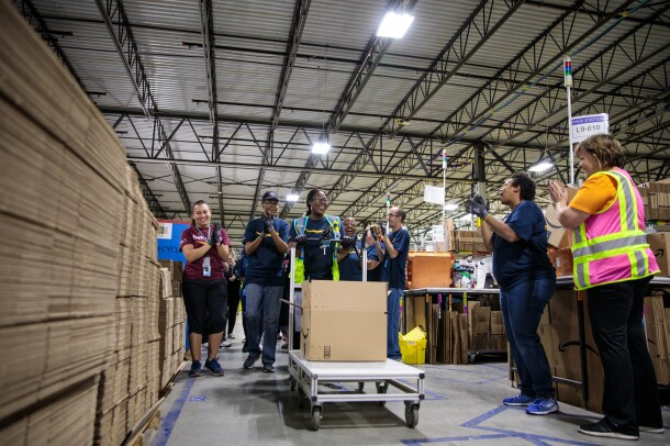 Eight people are pictured standing in a large warehouse space. At the center of the image, a woman pushes a metal cart carrying a cardboard box marked with the Amazon logo.