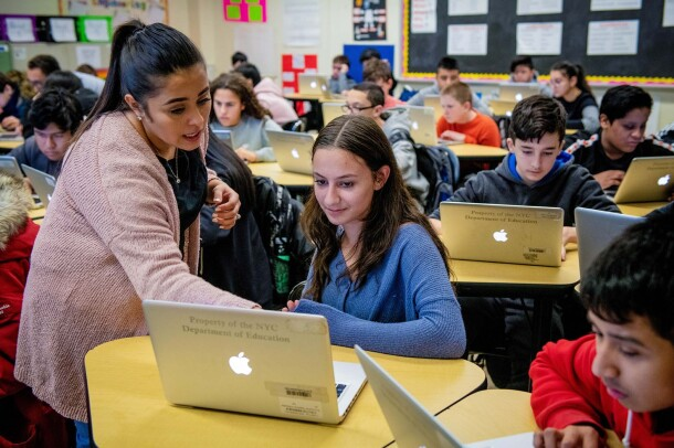 Students work on coding programs on laptop computers in a classroom at a New York City school.