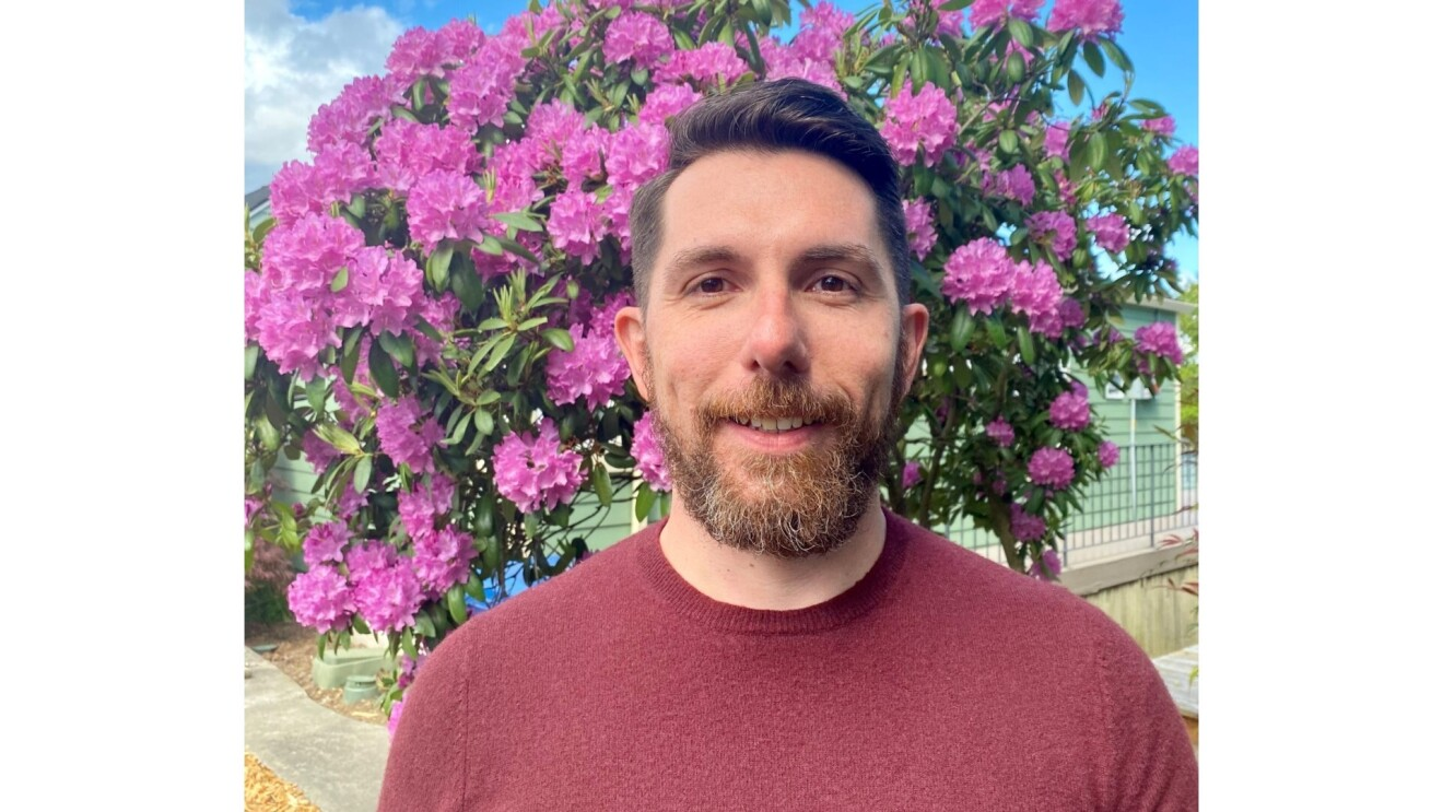 Fabio smiling, wears a red long-sleeved shirt has a beard. He is standing in front of a tree with purple flowers.