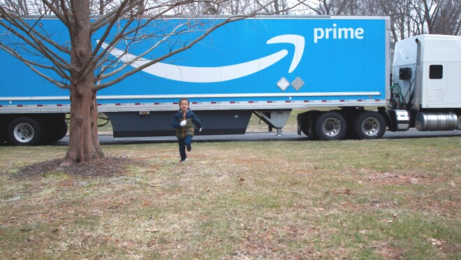 A boy runs across a lawn near a tree. Just behind him is a parked semi truck with the Amazon Prime smile logo.