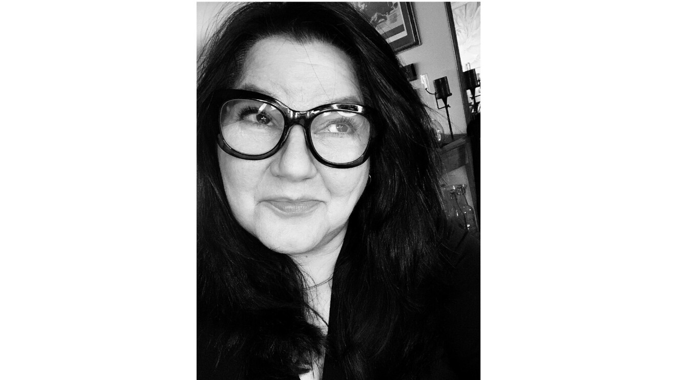 Bettina smiling and looking up in a selfie. She wears black framed glasses in a black and white photo.