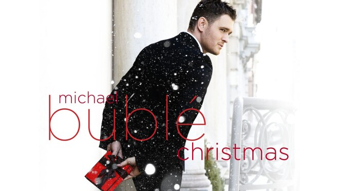 """Michael Buble stands outside wearing a tuxedo, facing away, but seeming to be glancing over his shoulder. he holds a small, wrapped gift in red paper with black bow. Snow is falling in the image, and text saying """"Michael Buble Christmas"""" is written over the top of the image."""