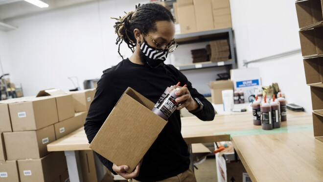 An employee of Capital City Mambo Sauce wears a face mask while filling a box with Capital City Mambo Sauce. Behind the employee are stacks of boxes.