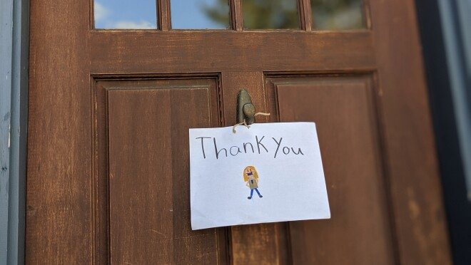 """A sign attached to the front door of a home, with a delivery driver wearing a mask, and """"Thank you"""" drawn on it."""