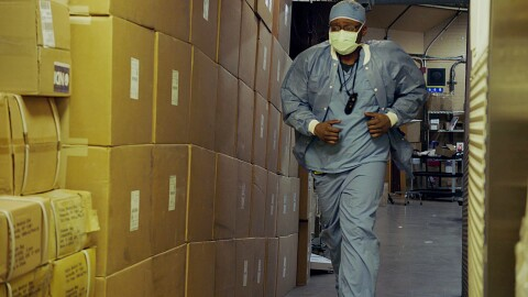A man wearing scrubs jogs alongside boxes of medical supplies.
