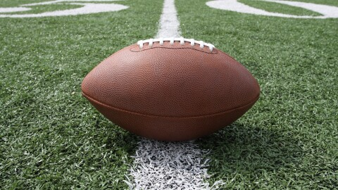 An image of a football sitting on top of a green football field with white yard markings.