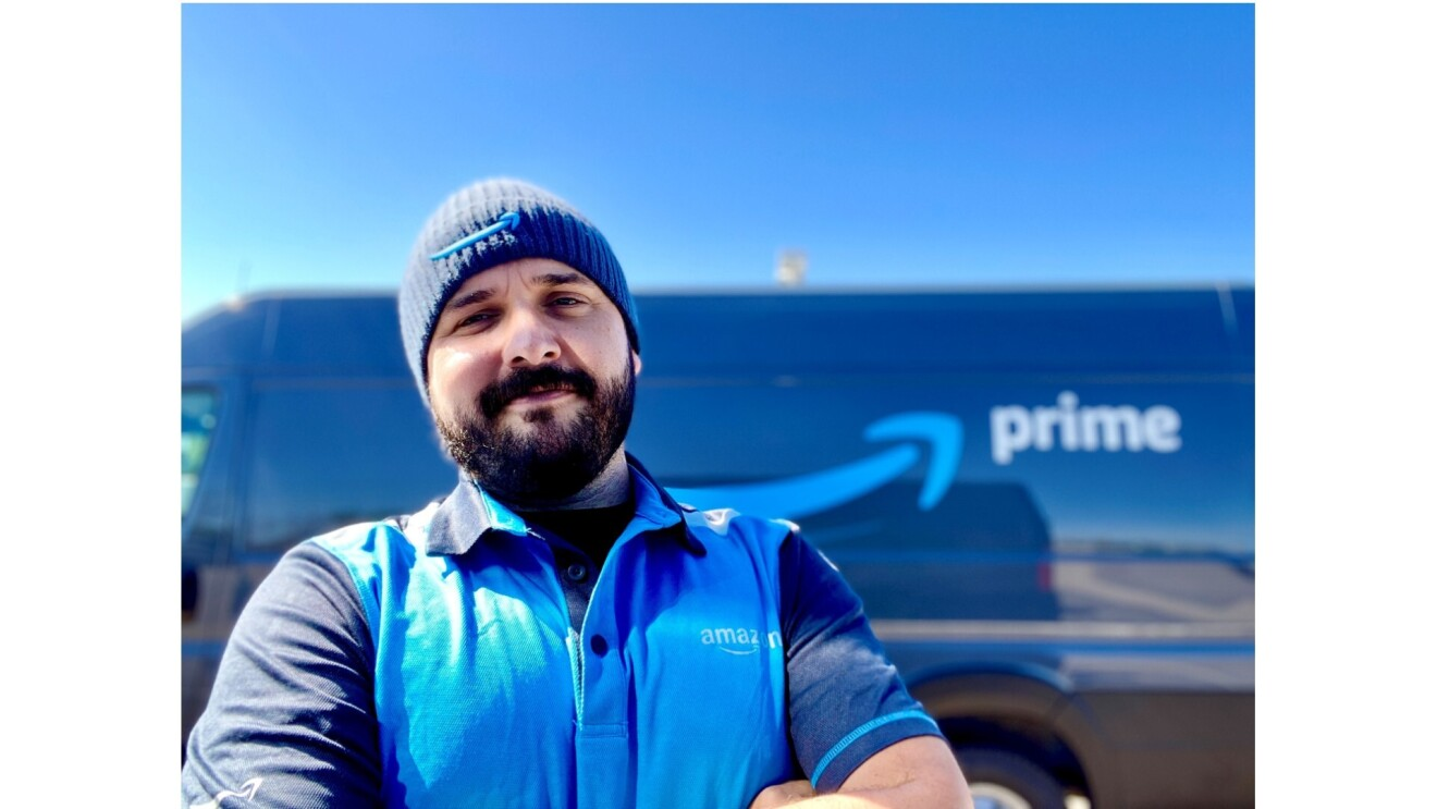 Nick Gallina smiles for the camera in front of his Prime delivery van. He is wearing a blue collared T-Shirt with an Amazon logo and a blue beanie with an Amazon logo.