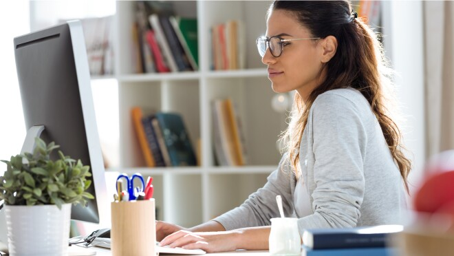 A woman wearing glasses sits at a computer, she is looking at the monitor and her hands are on the keyboard.