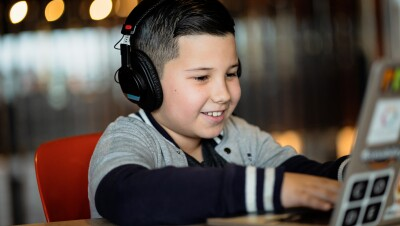 A boy works on a laptop at a coding camp while smiling