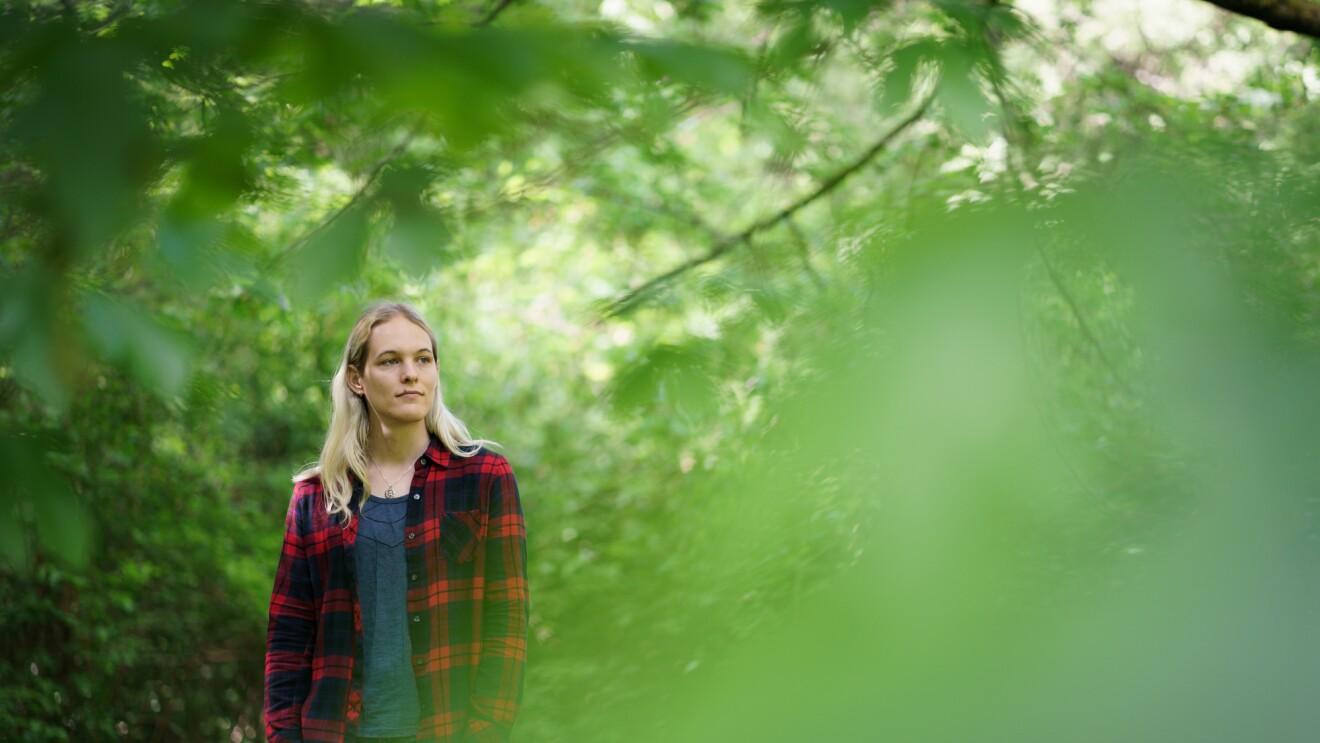 Danielle Skysdottir stands among leafy green trees. She has long blond hair and wears a T-shirt, a flannel shirt, and jeans.