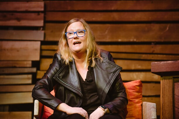 """A woman, Becky Gansert, speaking to the crowd from the stage at Amazon """"Live at the Ryman."""""""