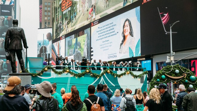 An image of the Harlem Gospel Choir on top of a green double-decker bus singing to crowds in New York.