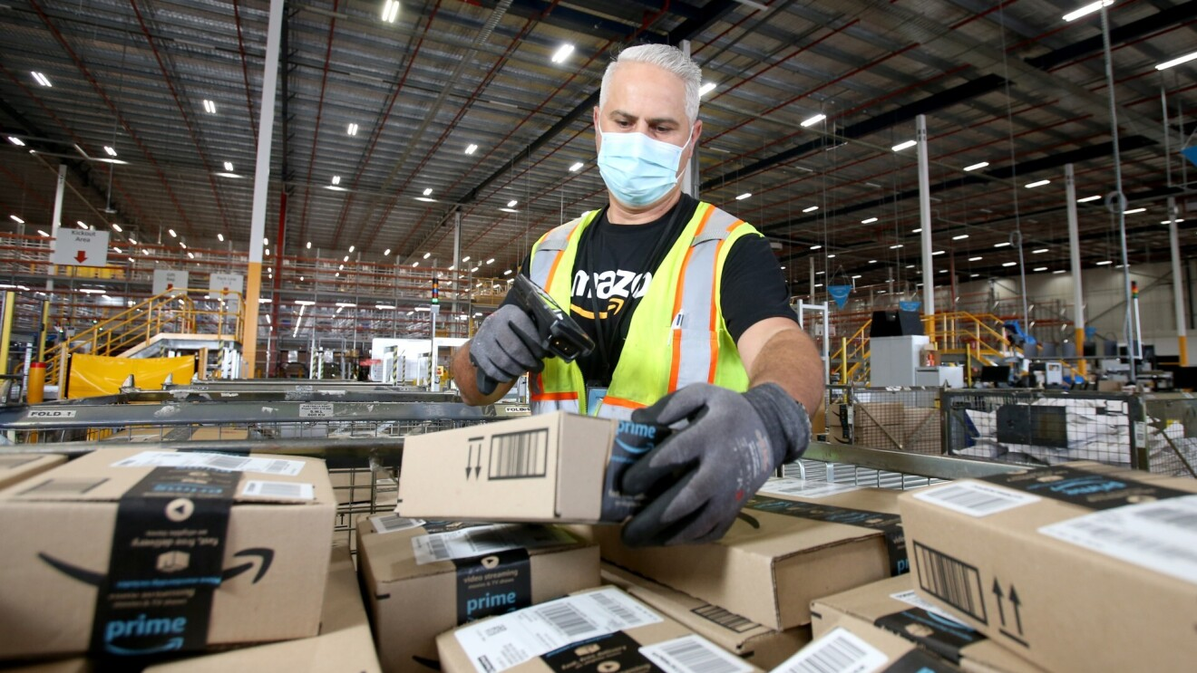 An Amazon employee scans packages in a fulfilment centre. He wears a black Amazon T-Shirt with a neon safety vest, and a face mask.