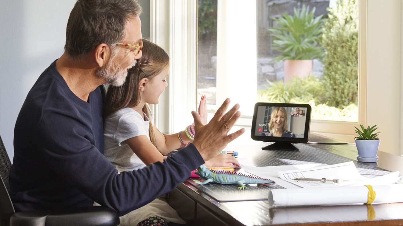 A grandfather sits in front of an Echo device with his granddaughter on his lap while they wave to someone they're calling on a video call.