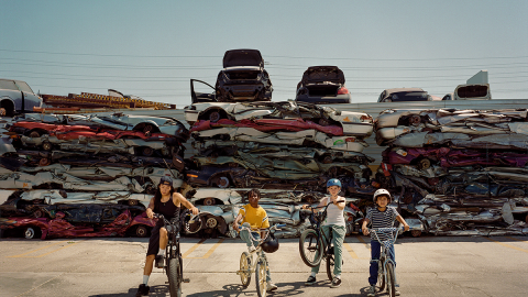An image of four kids standing on their bikes while looking at the camera. Behind them is a junkyard of smashed cars.