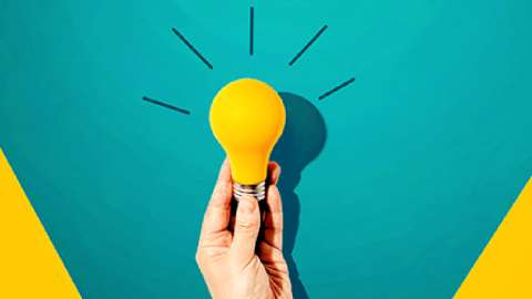 A hand holds a lightbulb in front of an aqua and yellow background. The bulb is yellow, and has illustrated lines coming off of it.