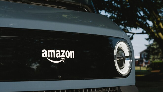 Detail of the front of an electric delivery vehicle, showing the Amazon logo a headlight.