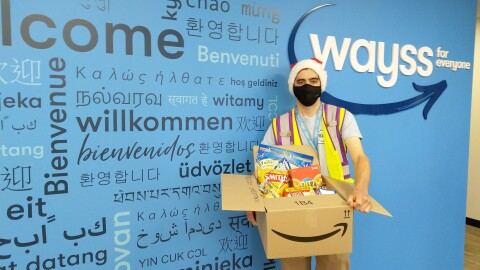 """An image of an Amazon employee holding a box of donations. He is standing in front of a wall with the """"Wayys"""" logo on it and is wearing a Santa hat, a face mask, and a safety vest."""