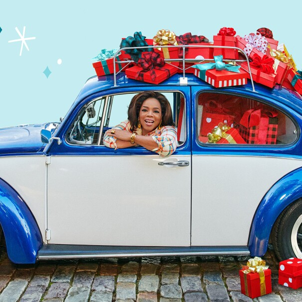 An image of Oprah smiling while looking out the window of a blue car. The car has presents stacked on top of and inside of it.