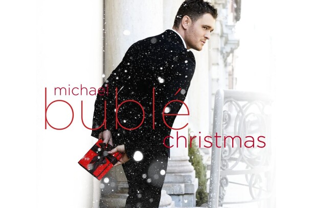 "Michael Buble stands outside wearing a tuxedo, facing away, but seeming to be glancing over his shoulder. he holds a small, wrapped gift in red paper with black bow. Snow is falling in the image, and text saying ""Michael Buble Christmas"" is written over the top of the image."