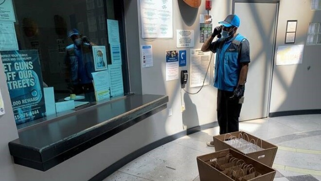 A delivery driver tasks on a landline phone while standing near two boxes filled with individual bags.