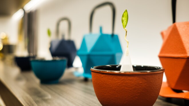 Teapots and teacups in various colors sit on a shelf.