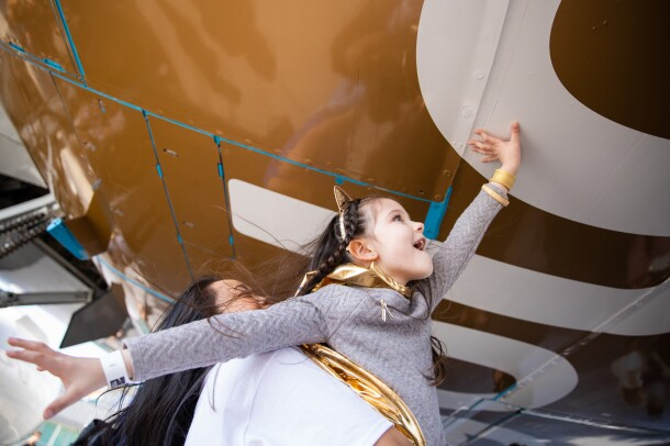 """A young girl wearing a gold cape, gold cat ears, and braids in her hair, reaches up (with help from a woman) to touch the bottom of a Prime Air aircraft with """"Go Gold"""" messaging."""