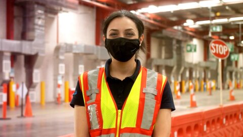 Daniella, an operations lead, stands in a fulfilment centre wearing a mask and a safety vest, looking at the camera.