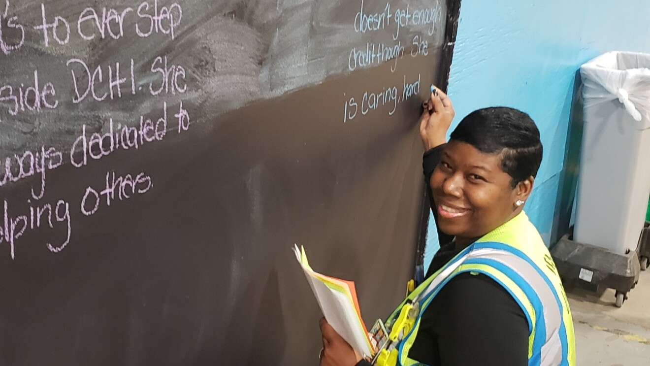 Amazon associate Tonisha Williams writes on a chalk board at an Amazon fulfillment center.