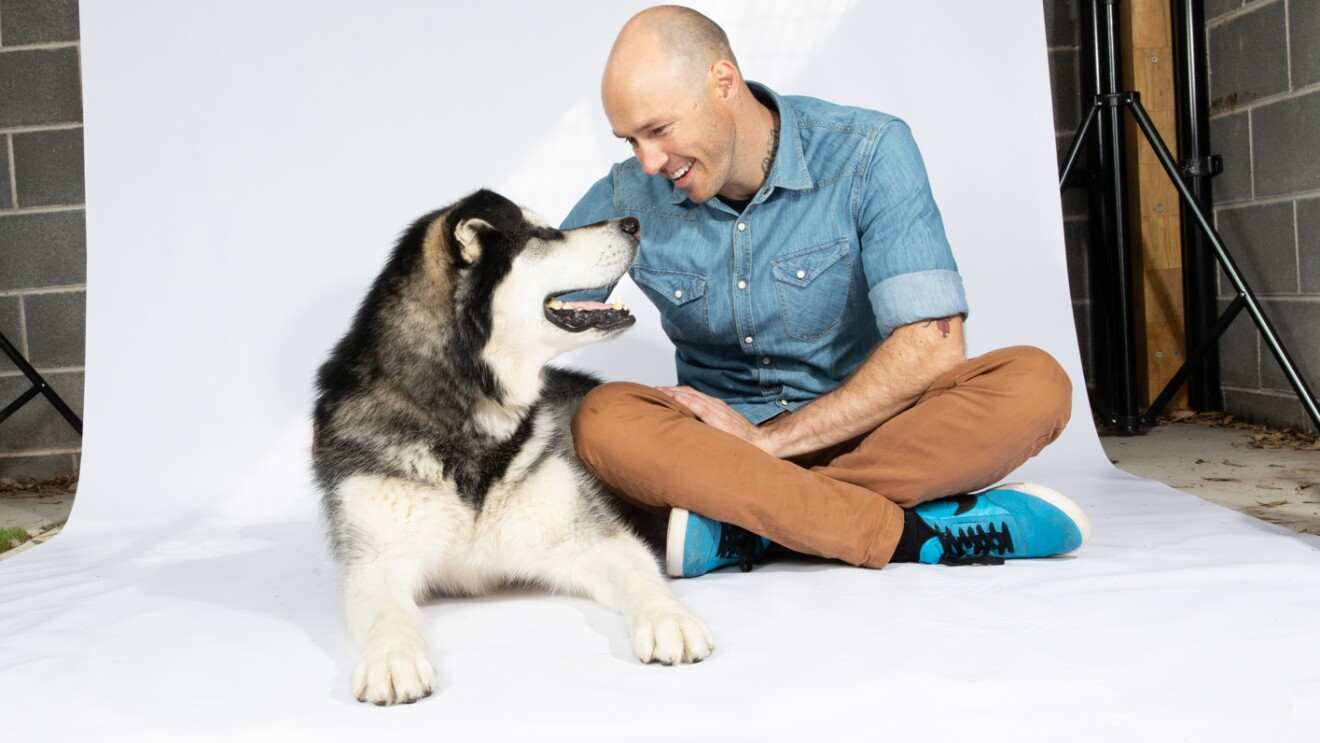 A man sitting on a white backdrop, wearing denim shirt, khakis and tennis shoes, leans down to pet a husky dog, who looks up at the man.